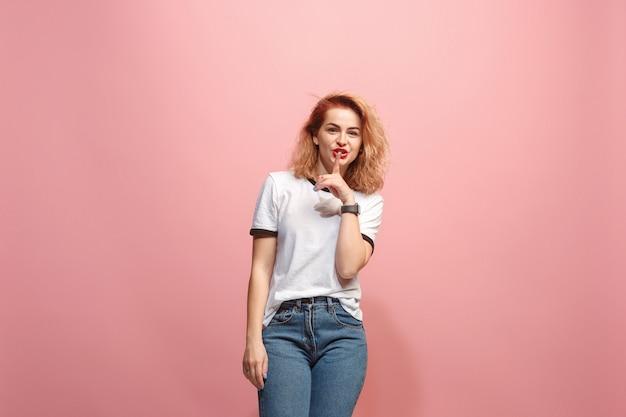 La joven mujer susurrando un secreto detrás de su mano sobre fondo rosa