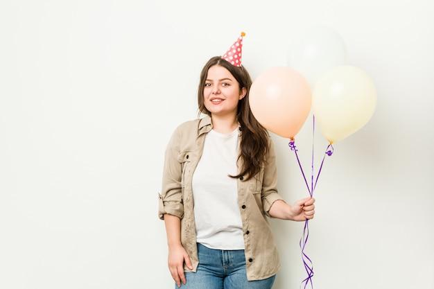Joven mujer de talla grande con curvas celebrando un cumpleaños feliz, sonriente y alegre.