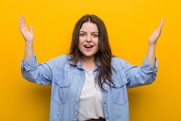 Joven mujer de talla grande con curvas que recibe una agradable sorpresa, emocionada y levantando las manos.