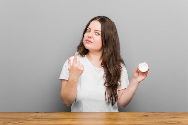 Joven mujer de talla grande con curvas que sostiene una crema hidratante apuntando con el dedo hacia usted como si invitara a acercarse.
