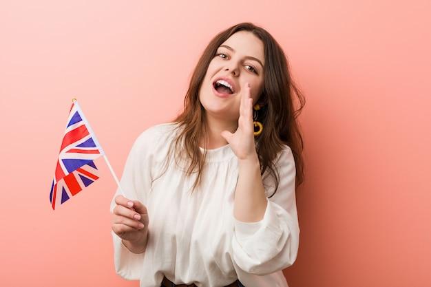 Joven mujer de talla grande con curvas sosteniendo una bandera del reino unido gritando emocionados al frente
