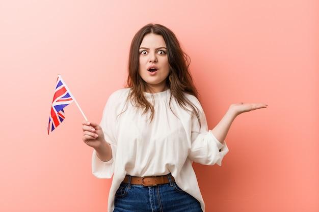 Joven mujer de talla grande con curvas sosteniendo una bandera del reino unido impresionado con copyspace palma.