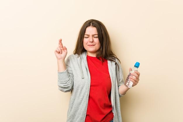 Joven mujer de talla grande con curvas sosteniendo una botella de agua cruzando los dedos para tener suerte
