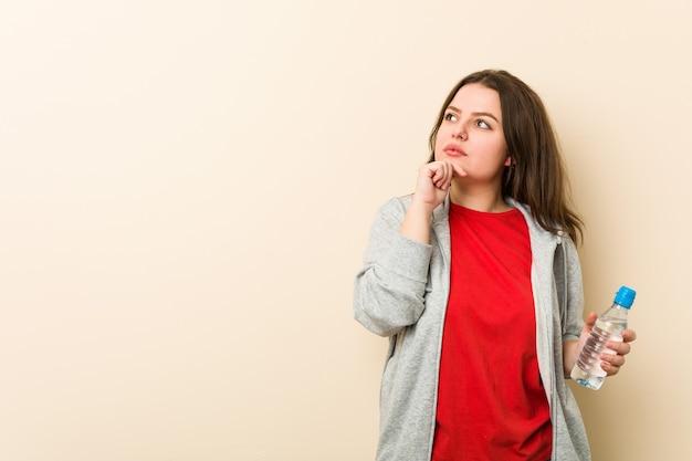 Joven mujer de talla grande con curvas sosteniendo una botella de agua mirando hacia los lados con expresión dudosa y escéptica.