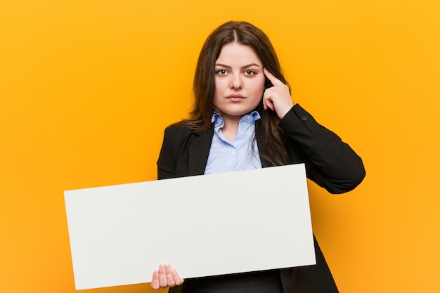 Joven mujer de talla grande con curvas sosteniendo un cartel apuntando su sien con el dedo, pensando, enfocada en una tarea.