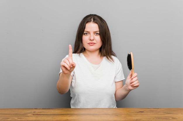 Joven mujer de talla grande con curvas sosteniendo un cepillo para el pelo que muestra el número uno con el dedo.