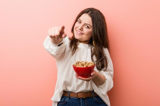 Joven mujer de talla grande con curvas sosteniendo un tazón de cereales sonrisas alegres apuntando al frente.