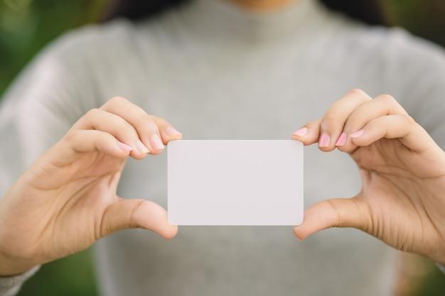 Joven mujer con tarjeta de crédito en blanco