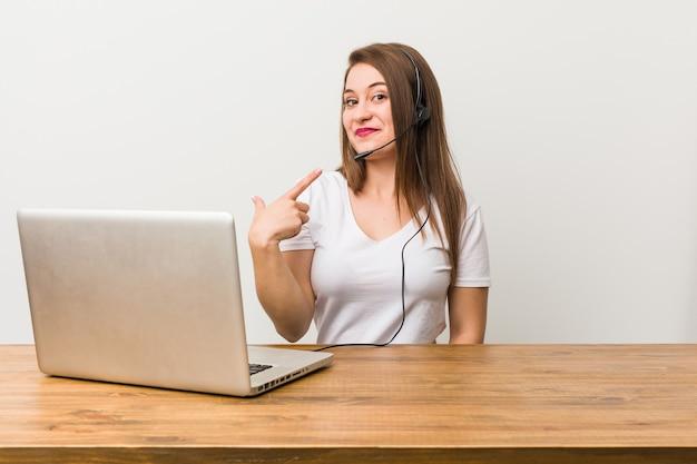 Joven mujer de telemercadeo apuntando con el dedo como si invitara a acercarse.