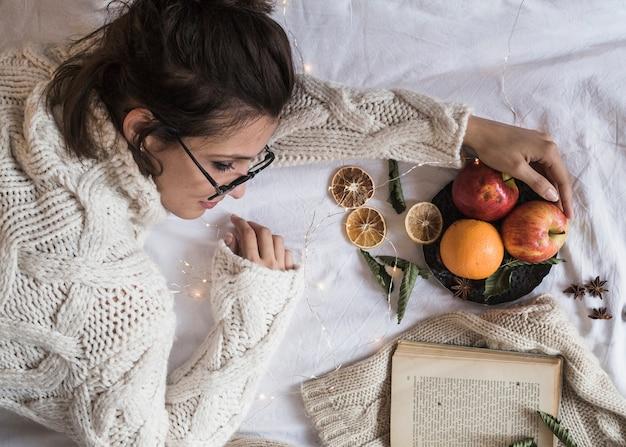 Joven mujer tendida sobre una manta con plato de frutas