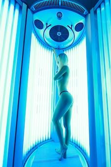 Una joven mujer toma el sol en un solarium bajo los rayos ultravioleta.