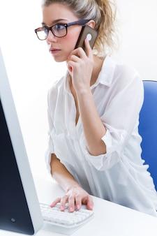 Joven mujer trabajando en casa en el equipo y hablando por teléfono con la oficina