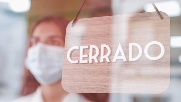 Joven mujer triste con máscara facial cambiando de signo de abierto a cerrado en español en la ventana para virus corona