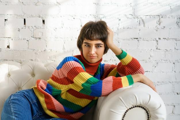 Una joven mujer está tumbada en un sofá con un suéter multicolor y calcetines