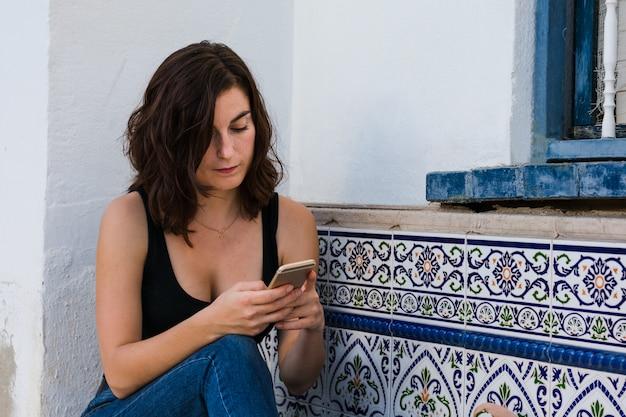 Joven mujer está usando su teléfono inteligente en la calle