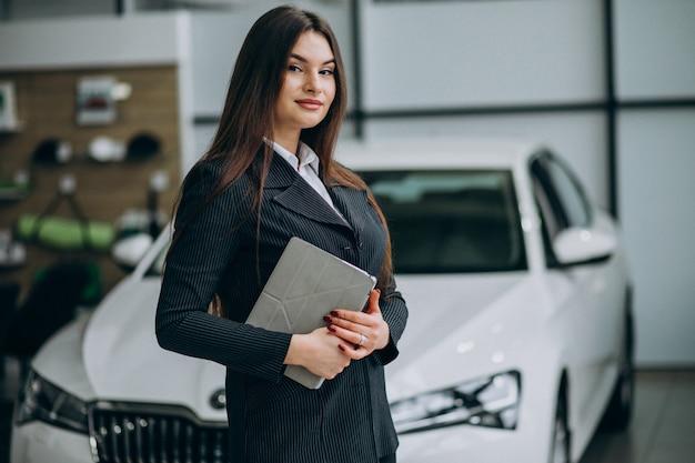 Joven mujer de ventas en carshowroom de pie junto al coche