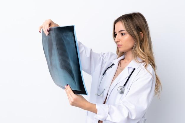 Joven mujer vestida con una bata de médico y sosteniendo una gammagrafía ósea