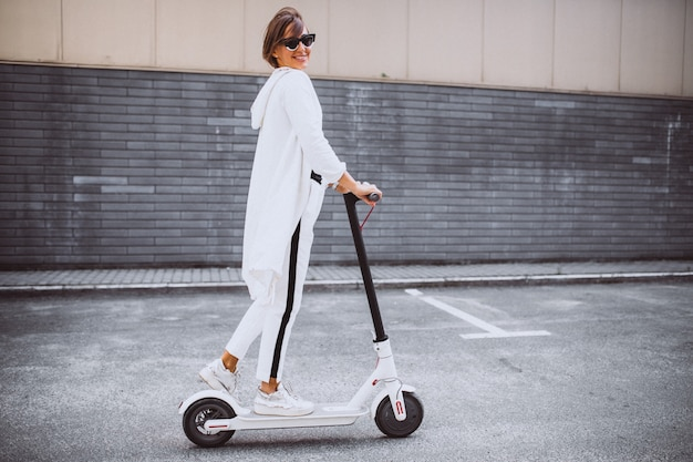 Joven mujer vestida de blanco scooter