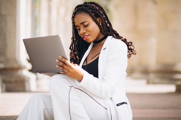 Joven mujer vestida de blanco usando laptop