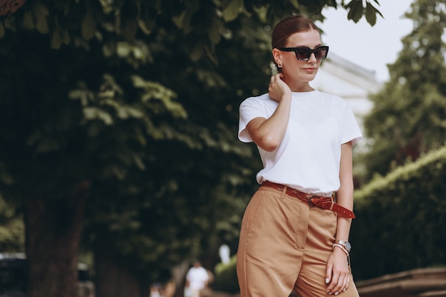 Joven mujer vestida casual afuera en el parque de la ciudad