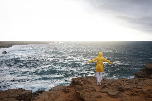 Joven mujer vestida con impermeable amarillo de pie con los brazos extendidos mientras disfruta del hermoso paisaje del mar en un día lluvioso en la playa de roca en clima nublado de primavera