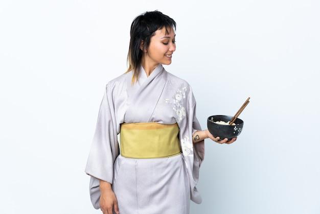 Joven mujer vestida con kimono sosteniendo un tazón de fideos sobre pared blanca con expresión feliz