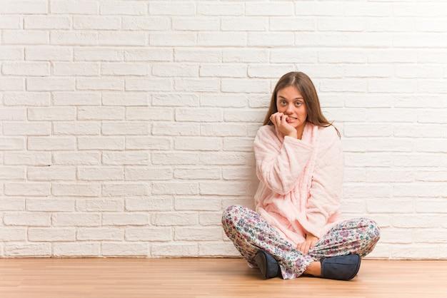 Joven mujer vestida con pijama mordiéndose las uñas, nerviosa y muy ansiosa