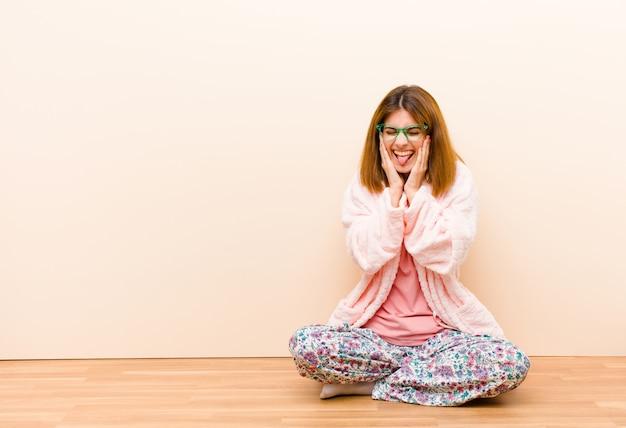 Joven mujer vestida con pijama sentada en casa luciendo tonta y divertida con una expresión tonta con los ojos cruzados, bromeando y bromeando