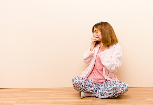 Joven mujer vestida con pijama sentado en casa sintiéndose enfermo con dolor de garganta y síntomas de gripe, tos con la boca cubierta