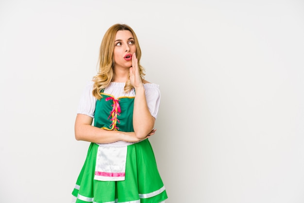 Joven mujer vestida con una ropa de día de san patricio aislada está diciendo una noticia secreta de frenado en caliente y mirando a un lado