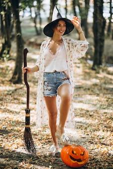 Joven mujer vestida con sombrero con escoba en halloween en el bosque