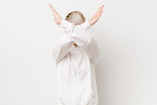 Joven mujer vestida con una sudadera blanca con los brazos cruzados