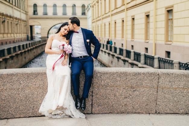 Joven mujer en vestido de novia blanco recibe beso de esposo
