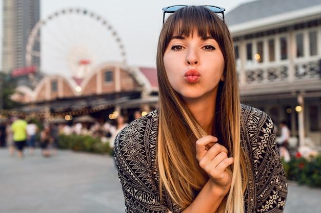 Joven mujer de viaje envía beso, pasando un buen rato en la ribera de bangkok