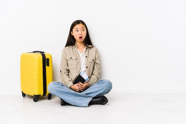 Joven mujer viajera china sentada sosteniendo una tarjeta de embarque sorprendida por algo que ella ha visto.