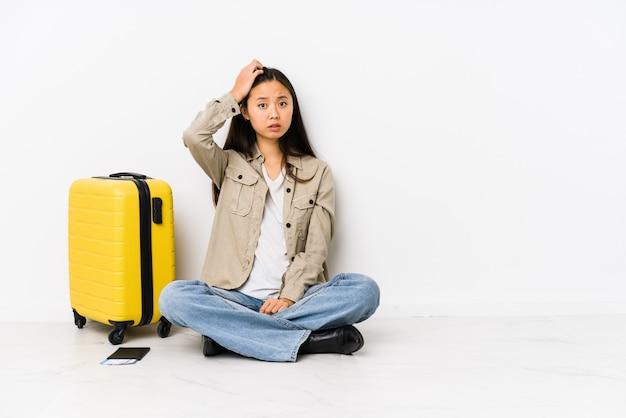 Joven mujer viajera china sentada sosteniendo una tarjeta de embarque sorprendida, ha recordado una reunión importante.