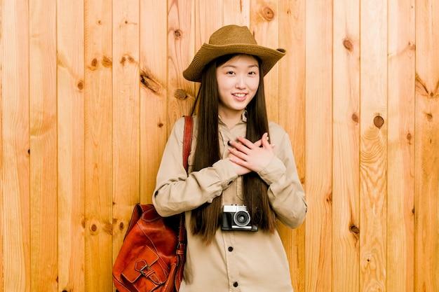 Joven mujer viajera china tiene una expresión amigable, presionando la palma contra el pecho