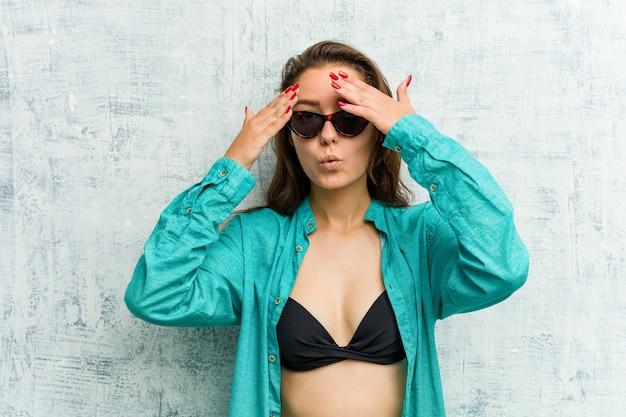 Joven mujer vistiendo bikini parpadea entre los dedos asustada y nerviosa