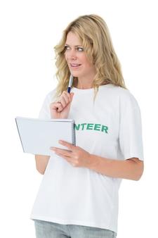 Joven mujer voluntaria escribiendo una nota