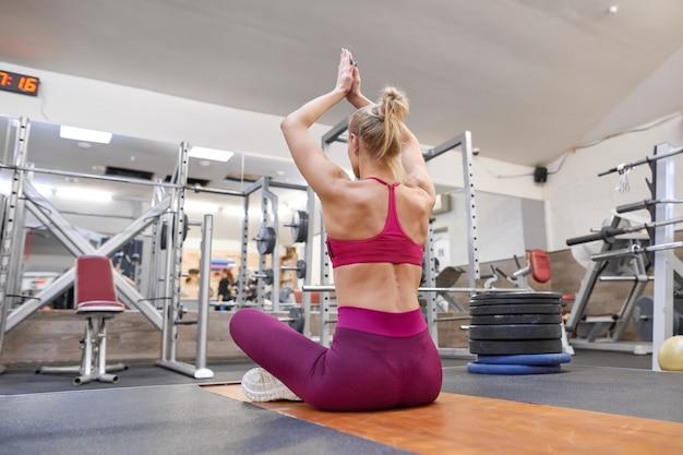 Joven musculosa atlética haciendo ejercicios de estiramiento en el gimnasio, mujer practicando yoga