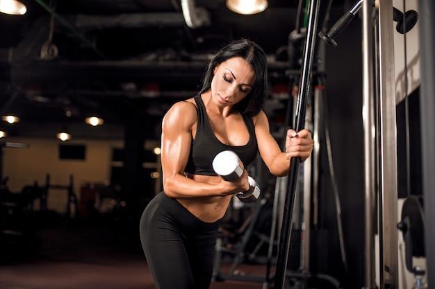 Joven musculosa haciendo ejercicio en el gimnasio