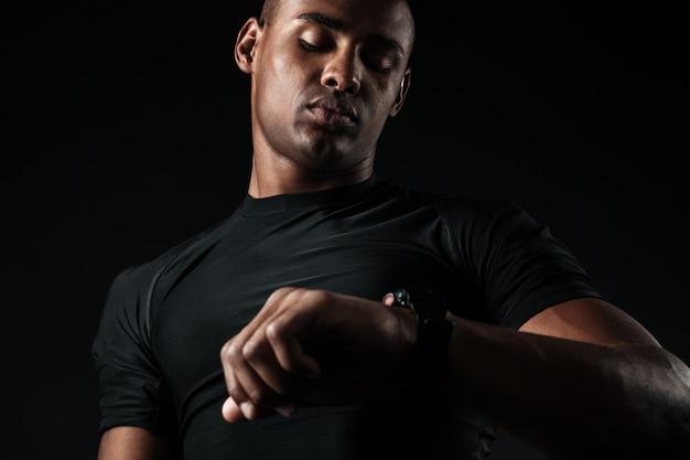 Joven musculoso africano mirando el reloj