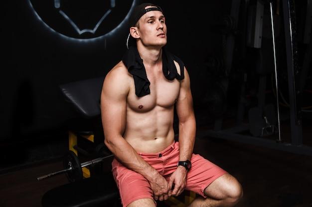 Joven musculoso, sin camisa, descansando en el gimnasio durante el entrenamiento, mostrando torso musculoso, pectorales y abdominales, sentado en el banco