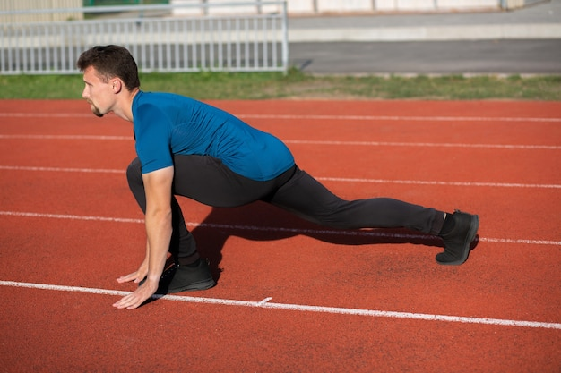 Joven musculoso haciendo estiramientos durante el entrenamiento en una pista de atletismo