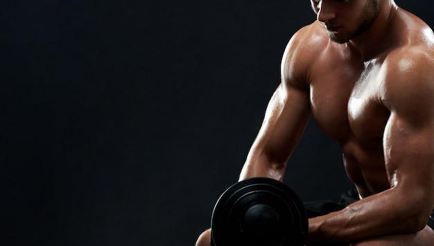 Joven musculoso levantando pesas sobre fondo negro