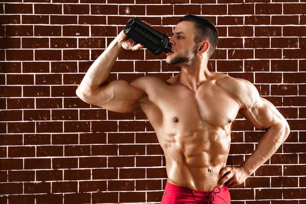 Joven musculoso mostrando su cuerpo perfecto y agitador