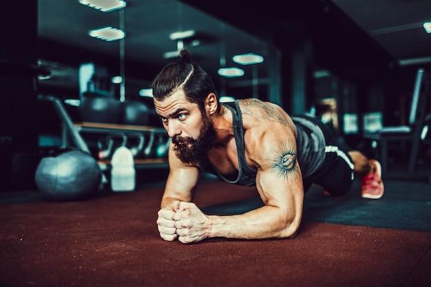 Joven musculoso vistiendo ropa deportiva y haciendo posición de tabla mientras hace ejercicio en el piso en el interior del desván