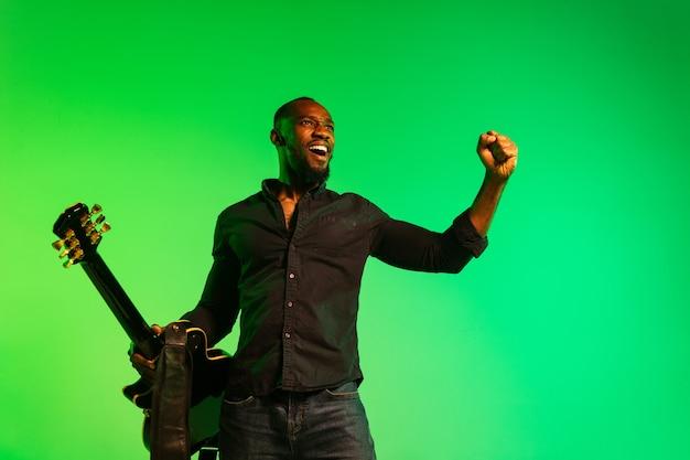 Joven músico afroamericano tocando la guitarra como una estrella de rock sobre fondo verde-amarillo degradado. concepto de música, afición, festival, al aire libre. chico alegre improvisando, cantando canciones.