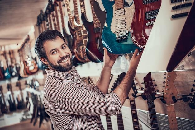 Joven músico barbudo compra guitarra eléctrica en tienda de música
