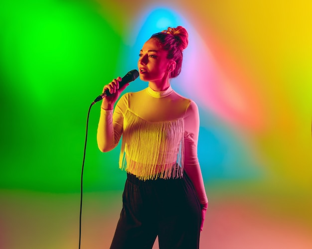 Joven músico caucásico jugando, cantando en gradiente de espacio en luz de neón. concepto de música, hobby, festival.